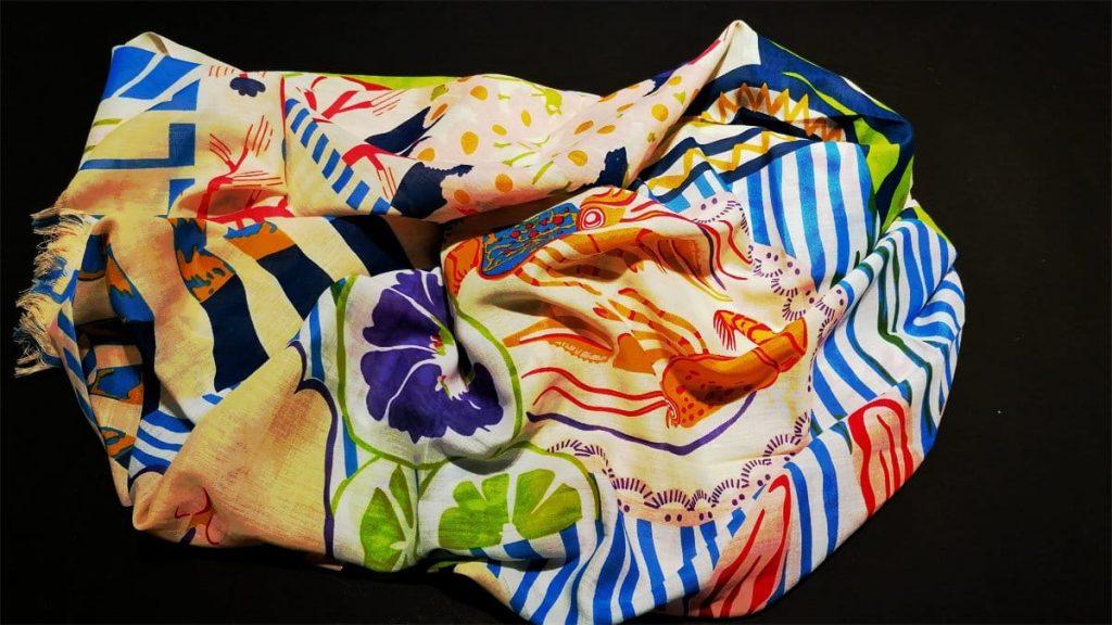 Farbenfroher Schal mit Blüten und grafischen Elementen